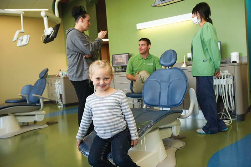 A girls smiles in the dental chair while Dr. Healy and her mom talk about the treatment at Tiny Teeth Pediatric Dentistry