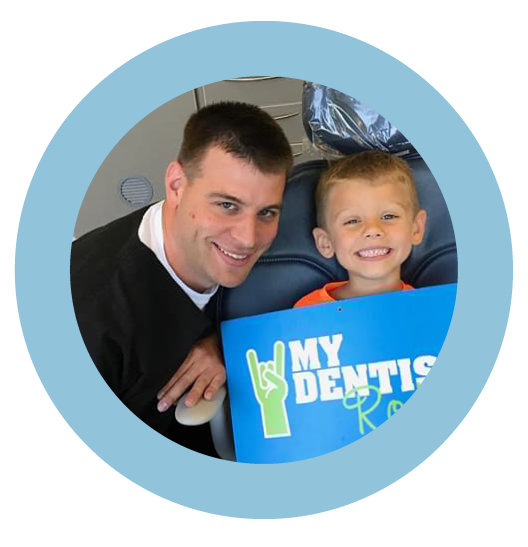 Dr. Healy smiling with child patient at Tiny Teeth Pediatric Dentistry