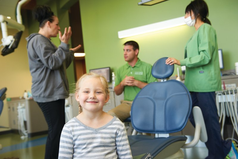 a girl smiling in the foreground after her treatment while her mother talks to Dr. Healy at Tiny Teeth Pediatric Dentistry