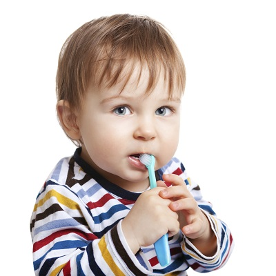 Baby in striped shirt holding a toothbrush in mouth at Tiny Teeth Pediatric Dentistry in Wichita, KS